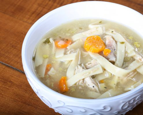 chicken noodle soup in a cream colored bowl ready to eat with large noodles